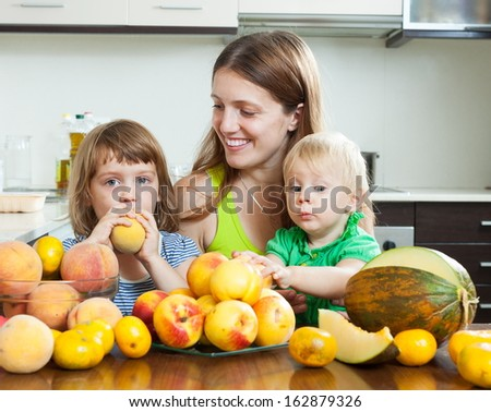 Happy family together with melon and peaches over dining table at home interior