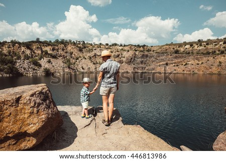 Happy family traveling together in nature park, forest, mountains, river, lake on sunny day. Woman and little baby on vacation. Beautiful landscape. Mother with child, kid in hats outdoors. Rear view.
