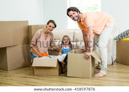 Happy family unpacking boxes while relocating in new house - stock photo