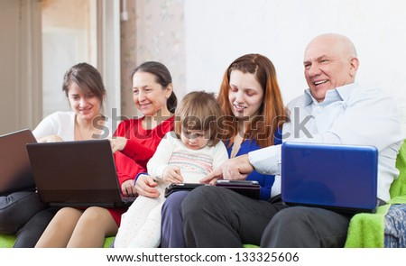 Happy family uses few electronic devices together - stock photo