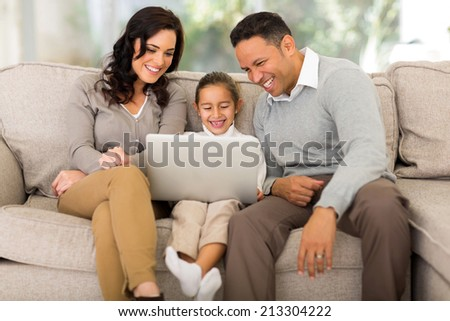 happy family using laptop in living room - stock photo