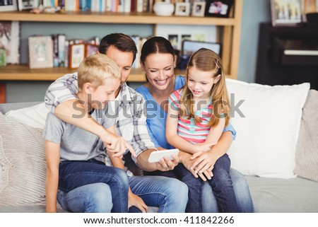 Happy family using mobile phone while sitting on sofa at home - stock photo