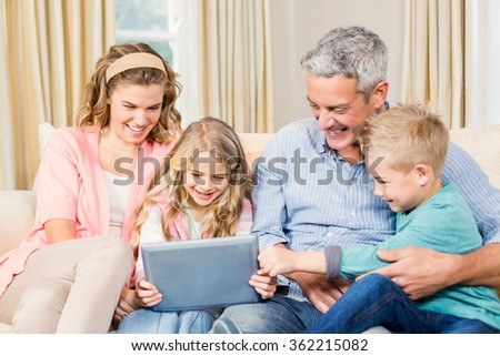 Happy family using tablet on the sofa at home - stock photo