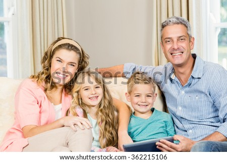 Happy family using tablet on the sofa in the living room