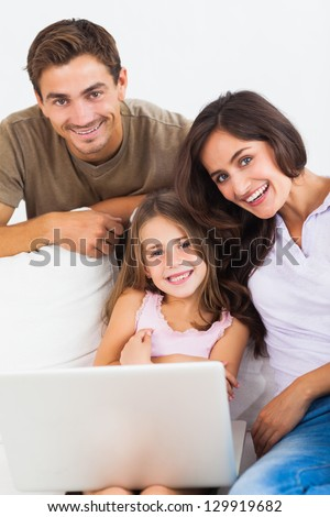 Happy family using the laptop sitting on a sofa
