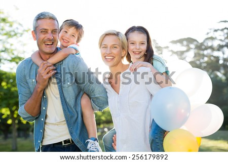 Happy family walking at the park on a sunny day - stock photo