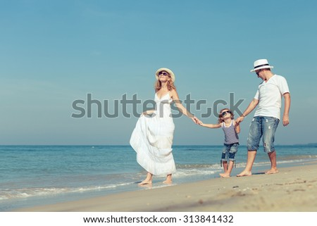 Happy family walking on the beach at the day time. Concept of friendly family. - stock photo