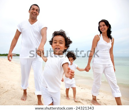 Happy family walking on the beach - togetherness concept - stock photo