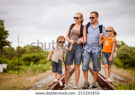 Happy family walking on the railway at the day time. Concept of friendly family.