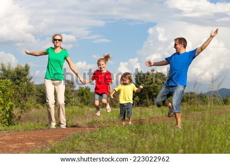 Happy family walking on the road at the day time. Concept of friendly family.