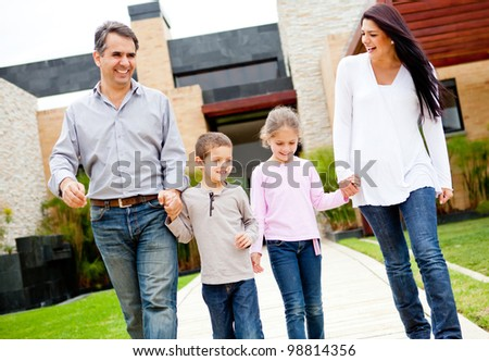Happy family walking outside their home and smiling - stock photo