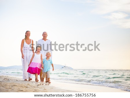 Happy Family Walking Together by the Beach - stock photo
