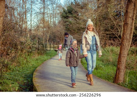 Happy family walking together holding hands over a wooden pathway into the forest - stock photo