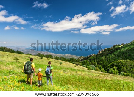 Happy family walking with backpacks on field and looking at the sea