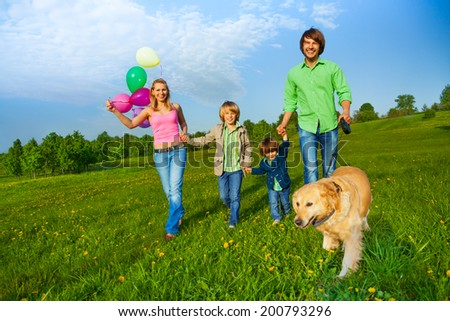 Happy family walks with balloons and dog in park - stock photo