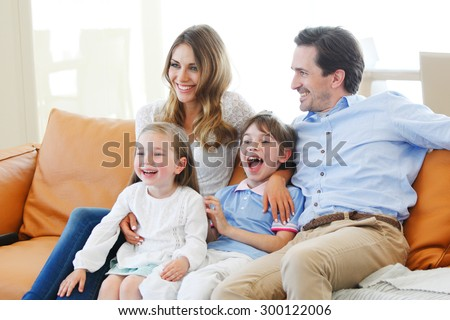 happy family watches movie while sitting on the couch - stock photo