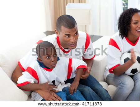 Happy family watching a football match at home - stock photo