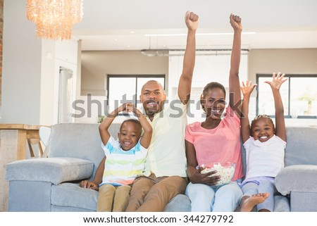 Happy family watching television eating popcorn in living room - stock photo