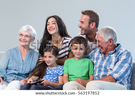 Happy family watching television sitting on a sofa in the living room