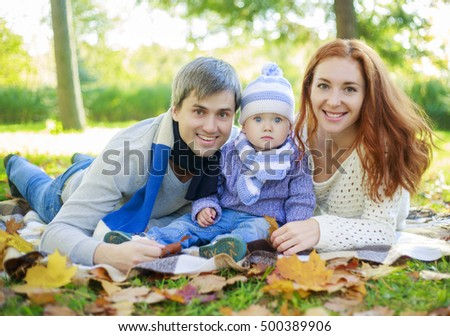 happy family with a baby in the park on a warm autumn day