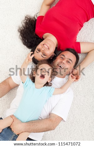 Happy family with a child laying on the floor - top view
