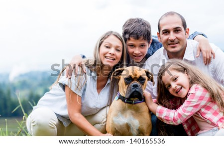 Happy family with a dog enjoying the countryside lifestyle - stock photo