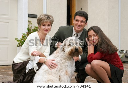 Happy family with a dog in front of the home - stock photo