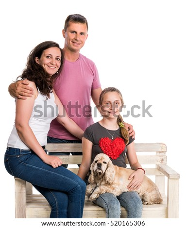 Happy family with a pet dog sitting on a bench and posing on a white background