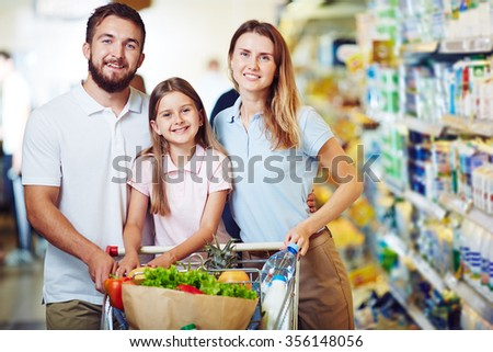Happy family with a shopping cart - stock photo