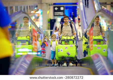 happy family with baggage on conveyor in airport, ready to travel - stock photo