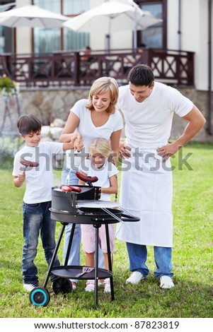 Happy family with barbecue outdoors - stock photo
