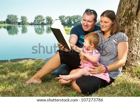 Happy family with books on the nature near lake - stock photo
