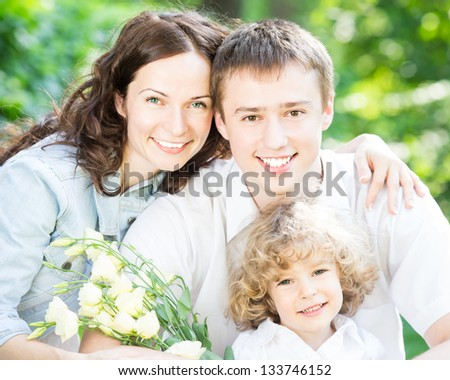 Happy family with bouquet of flowers having fun outdoors in spring park against natural green background. Mothers day celebration concept - stock photo