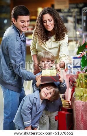 Happy family with boxes of gifts in shop - stock photo