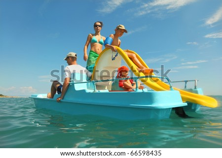 happy family with boy and girl on pedal boat with yellow slide in sea, view from water, shot from waterproof case