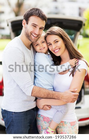 Happy family with car on background  - stock photo