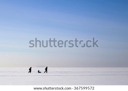 Happy family with child are sledding on the frozen lake