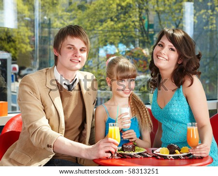 Happy family with child in restaurant.