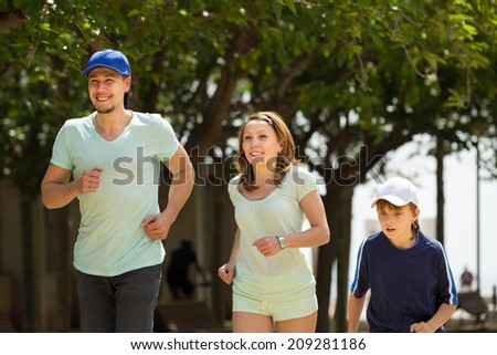 Happy family with child running in park and smiling - stock photo