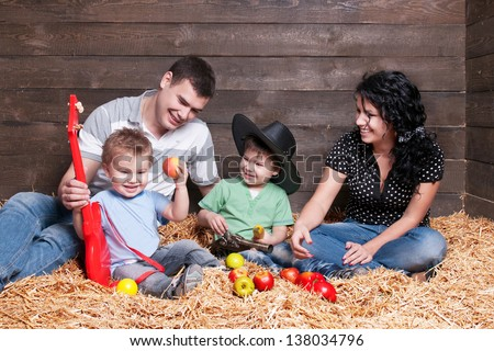 Happy family with children  - beautiful mother and father hug their sons, posing on hay  in studio closeup - stock photo