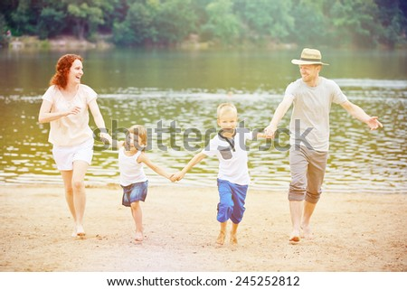 Happy family with children having summer vacation at lake with beach - stock photo
