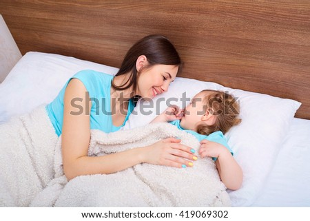 Happy family with children in bed. Mother and daughter smiling in the bed.