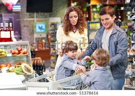 Happy family with children in grocery shop - stock photo