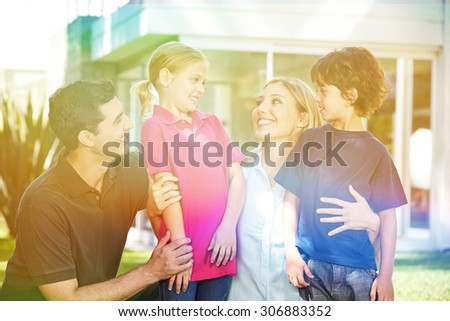 Happy family with children in summer in a garden in front of a house - stock photo