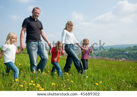 Happy family with Children walking down a meadow with dandelion flowers at a bright spring day, in the background a village is to be seen - stock photo
