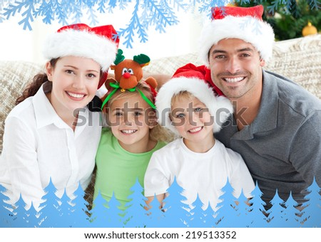 Happy family with christmas hats sitting on the sofa against frost and fir trees in blue - stock photo