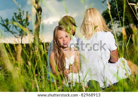 Happy family with daughter girl sitting in a meadow in summer before a storm - stock photo