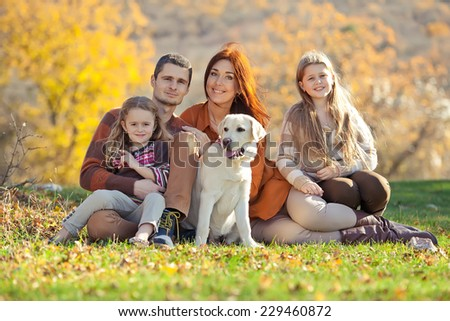 Happy family with dog on nature - stock photo