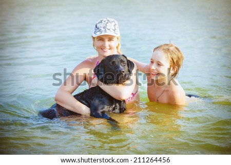 Happy family with dog playing in water - stock photo