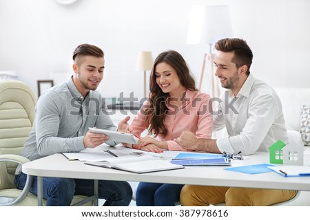 Happy family with estate agent,  in bright office - stock photo